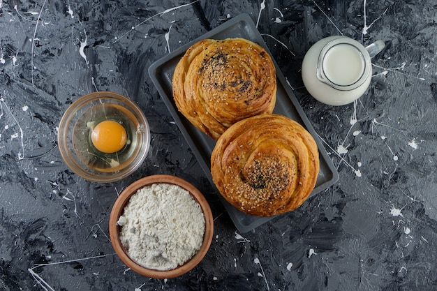 Azerbaijan national pastry with uncooked chicken egg and a glass pitcher of fresh milk