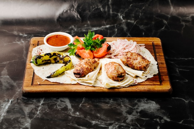 Azerbaijani beef barbecue kebab served on lavash with grilled pepper and tomatoes.
