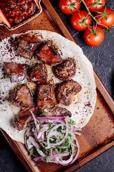 Azerbaijani beef kebab in lavash bread with onion salad and bbq sauce.