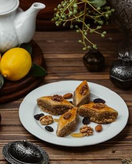 Azerbaijani dessert pakhlava with nuts and sultana inside white plate.