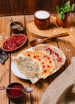 Azerbaijani gutabs platter with herbs pumpkin and meat served with yogurt