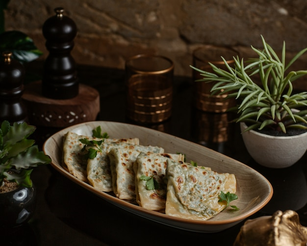 Azerbaijani kutab, gozleme finely roasted and served in a ceramic long plate