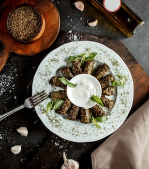 Azerbaijani long wrapped grape leaves dolma garnished with yogurt and dried mint leaves