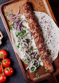 Azerbaijani lule kebab in lavash bread with onion green salad.