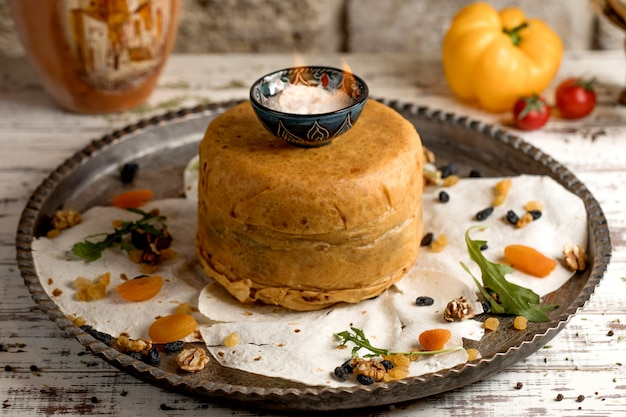 Azerbaijani pilaf in crusty dough, served in antique tray with dried fruits and arugula