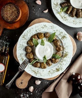 Azerbaijani round wrapped grape leaves dolma garnished with yogurt and dried mint leaves
