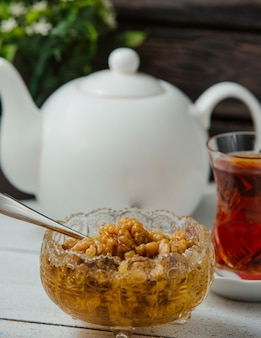 Azerbaijani walnut jam without skin, served with black tea in armudu glass