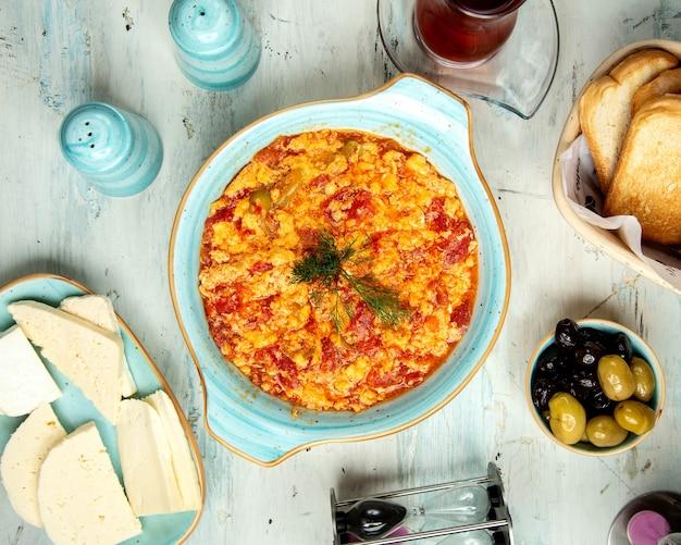 Азербайджанские традиционные яичницы с помидорами тарелка с сырами и оливками
