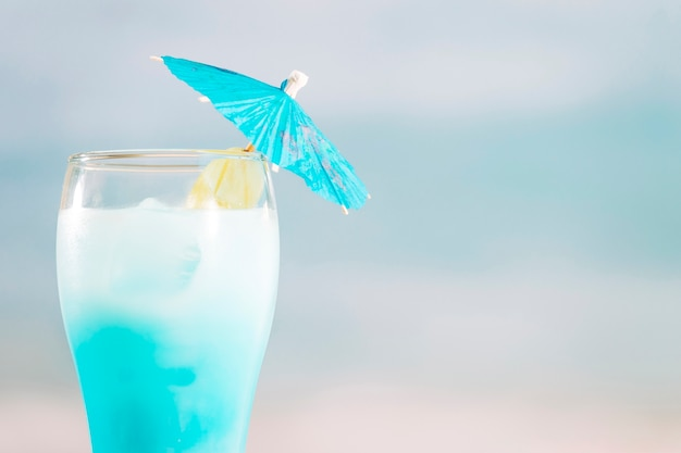 Azure cocktail with umbrella in glass