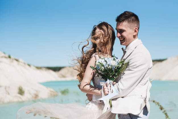 湖の近くの軽いスーツで新郎を抱いて美しいドレスを着た花嫁。戸外の砂の丘の上に立っている結婚式のカップル。ロマンチックなラブストーリー。地平線上の紺azureの水。