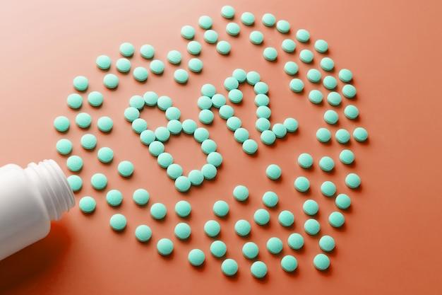 Витамины b 12 в форме сердца на красном субстрате, вылитые из белой банки.