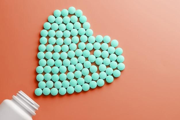 Витамины b 12 на красной сердцевидной основе, выливаемой из белой банки.