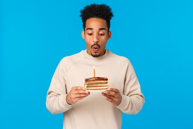 休日、お祝いのコンセプト。誕生日を祝って、願い事をしてケーキとブローアウトキャンドルを保持している陽気なアフリカ系アメリカ人のb-day男、うれしそうな青い背景に立って、パーティー