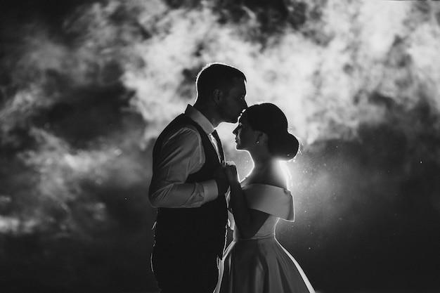スーツを着た彼女の強い夫と長い白いドレスを着た若い女性の白黒写真は煙で写真を撮る