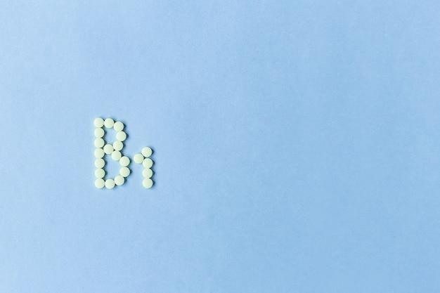 Желтые таблетки, образующие b1 на синем фоне