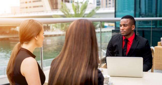 B2b встреча. деловые люди обсуждают работу в кафе на открытом воздухе.