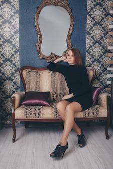 仕事のコンセプト、ビジネスをモデル化-ドレスを着た女の子のスタイリッシュな肖像画。モデルbはソファーに座っています。家の快適さ、レクリエーション、布張りの家具のコンセプト
