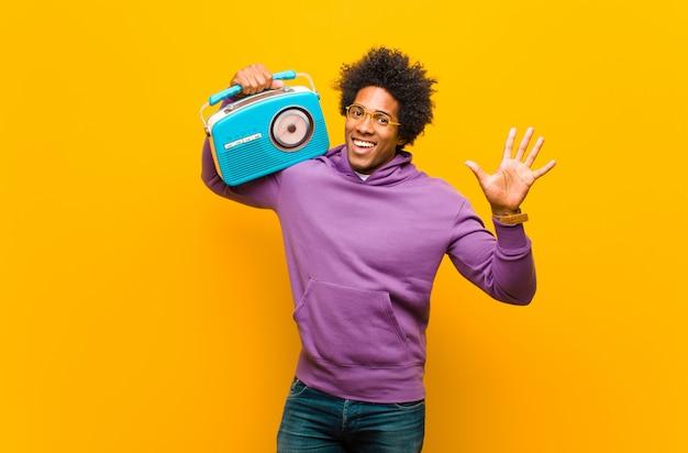 Молодой человек афроамериканца с винтажным радио против оранжевого b