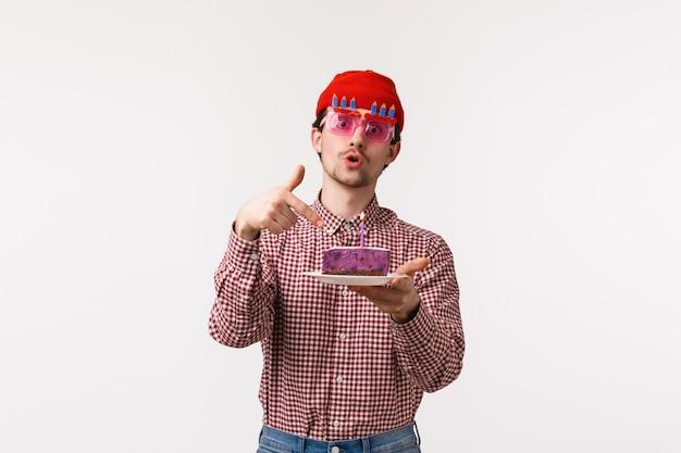 お祝い、休日、ライフスタイルのコンセプト。 bデーパーティーで楽しんで面白い陽気な男性流行に敏感な友人、メガネを着用し、キャンドル、白い壁を吹き消すように求めている誕生日ケーキを指して