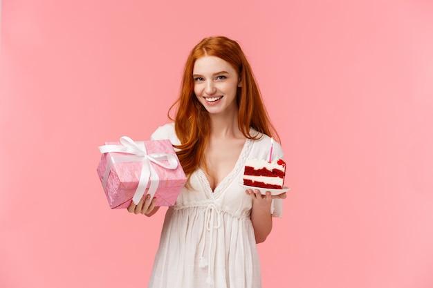 魅力的な赤毛のガールフレンドは素晴らしい誕生日パーティーを手配し、願い事をするように頼み、ろうそくを吹き、平和なbデーケーキとかわいいプレゼントを持って、笑顔の贈り物、ピンクの壁