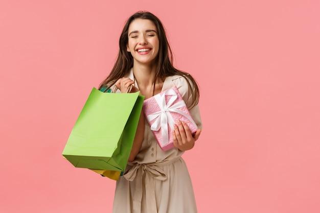 幸福、プレゼント、お祝いのコンセプトです。買い物を楽しんでいる陽気な幸せでのんきなbデーの女の子、素敵な一日の店、ホールドショップバッグとギフト、興奮して笑う目、ピンクの壁