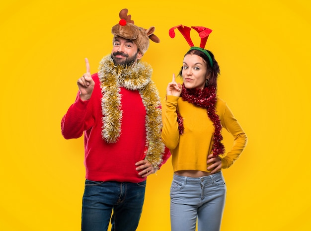 カップルは、表示され、bの看板で指を持ち上げてクリスマス休日のために服を着た