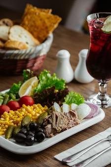 オリーブ、コーン、bでた牛肉、レタス、コルニション、トマト、レモンの前菜プレート