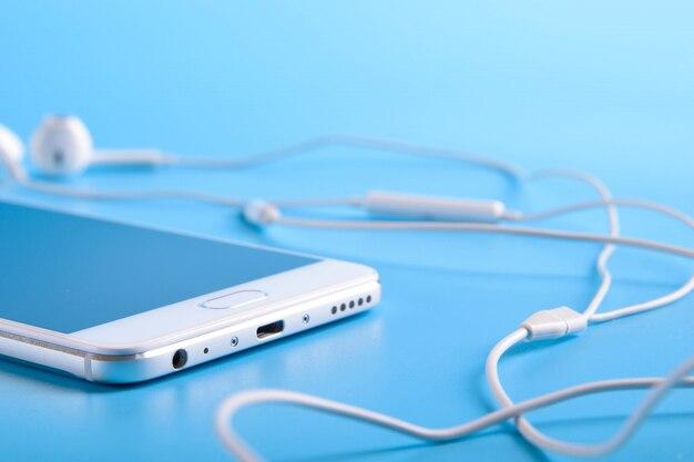 モバイルヘッドフォンと青bの青い携帯電話