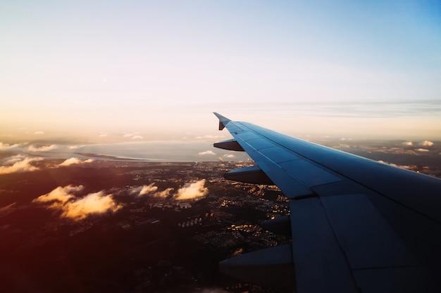 Вид из окна самолета над вечерним лиссабоном с небольшим количеством облаков b