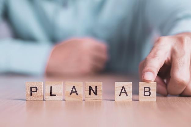 ビジネスマンは、木製のブロック、ビジネス成功創造的な動機の概念に計画bの単語を選択します