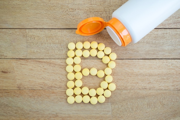 木製の背景にbアルファベットに形を形成する黄色の丸薬
