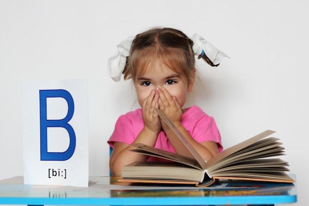 Буква «б» как книга. милая маленькая девочка читает книгу и держит бумагу с буквой b