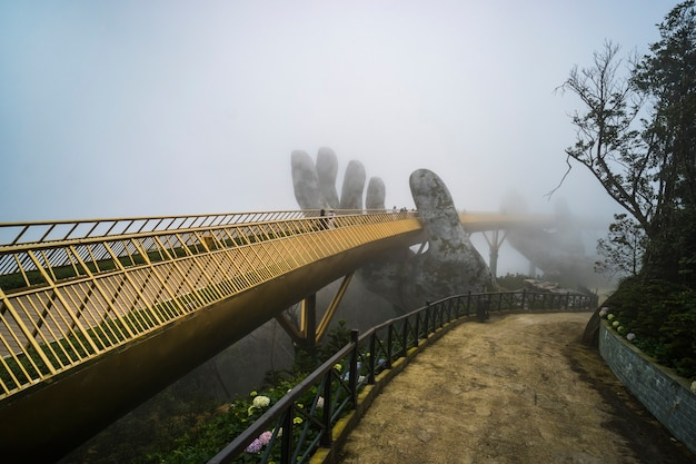 베트남 다낭시 바나힐 마운틴 리조트. 베트남 다낭의 안개 낀 날 바나힐의 관광 리조트에서 황금 다리를 두 개의 거대한 손으로 들어 올립니다.