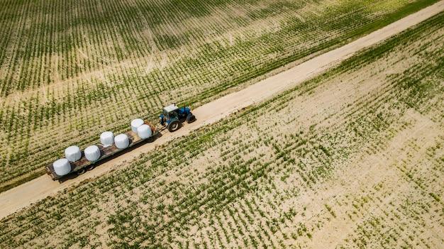 トラクターはフィールドに乗って干し草の空撮のbaを運ぶ