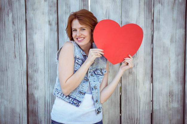 木製baackgroundに対して心を持って笑顔の流行に敏感な女性