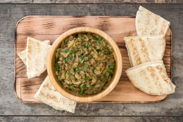 Baba ganoush in bowl and pita bread on wooden table, top view