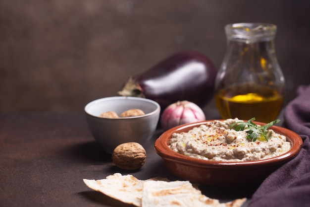 Baba ganoush, ezme levantine oriental cuisine in a plate during preparation with a selection of products: eggplant, butter, walnuts and pita bread. copy space