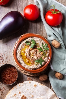 Baba ganoush from baked eggplant with sesame paste with eggplant, spices and walnuts and herbs, tomatoes