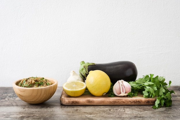 Baba ganoush and ingredient in wooden bowl on wooden table