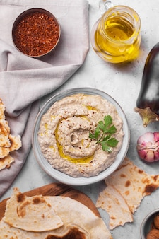 Баба гануш закуска левантийской кухни из запеченных баклажанов и кунжутной пасты с травами, специями и оливковым маслом и ингредиентами на бетонном фоне с крупным планом лаваша