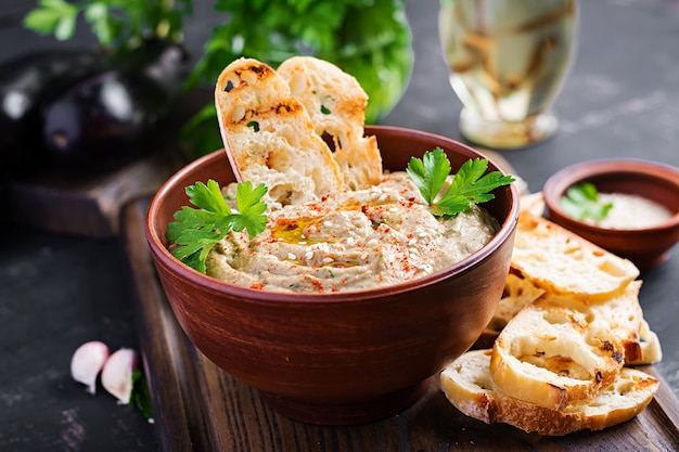 Baba ghanoush vegan hummus from eggplant with seasoning, parsley and toasts. baba ganoush. middle eastern cuisine.