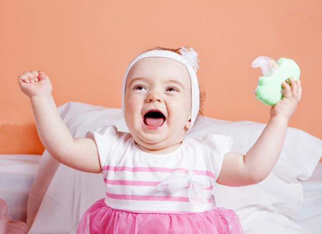 笑うおもちゃで遊ぶ可愛い女の子。一年。