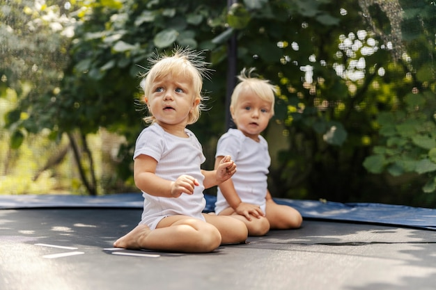 Babes and a trampoline. cute babies in white baby bodysuits are playing in the yard and jumping on the trampoline. toddlers with blonde hair and blue eyes. growing up in the home yard. charged hair