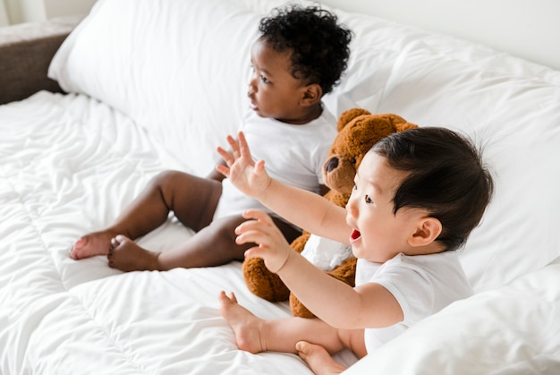Babies sitting on the bed