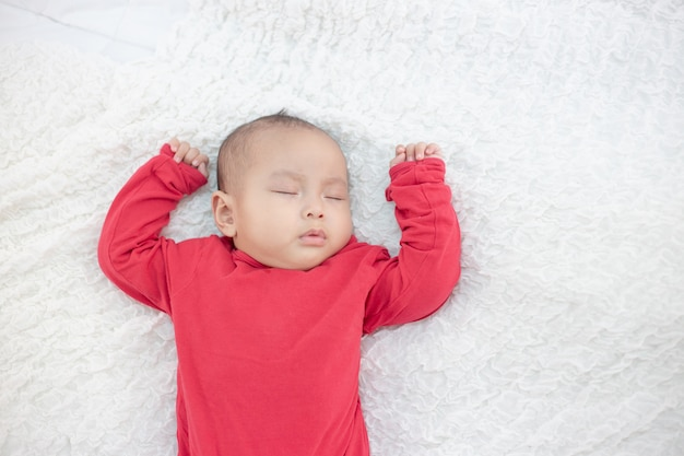 Babies wearing red shirts sleeping in bed