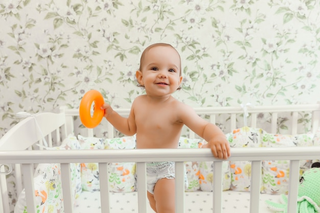A baby of 11 months in a diaper stands in his crib. child in the bed.