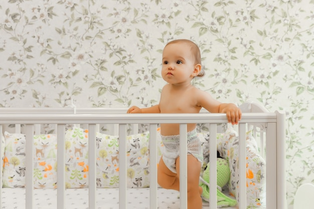 A baby of 11 months in a diaper stands in his crib child in the bed