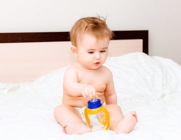 生後6か月の赤ちゃんは、ベッドに横になってボトルから水を飲みます。幸せで楽しい赤ちゃん