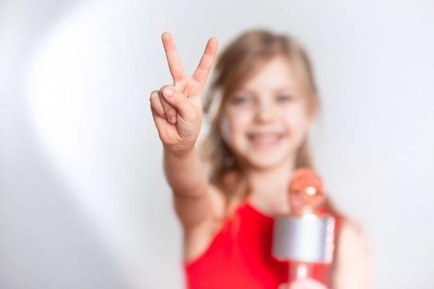 Baby 7 - 8 years old, cute charming blonde girl with blond hair sings in the device, bluetooth microphone and smiles on a gray wall. shows cool with two fingers
