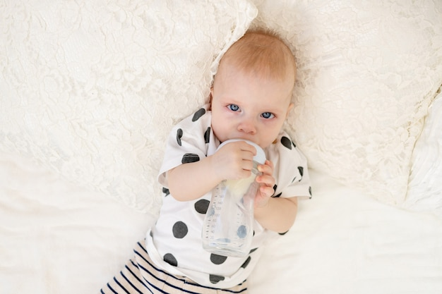 Baby 8 months old lying on the bed in pajamas and drinking milk from a bottle, baby food concept, top view, place for text